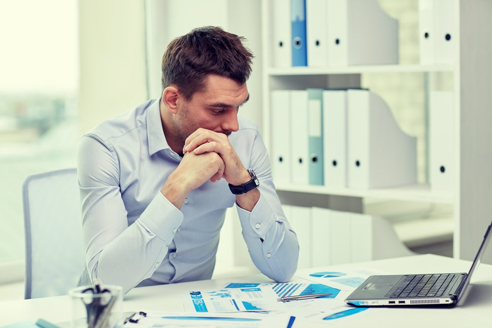 Man with anxiety sitting at work desk