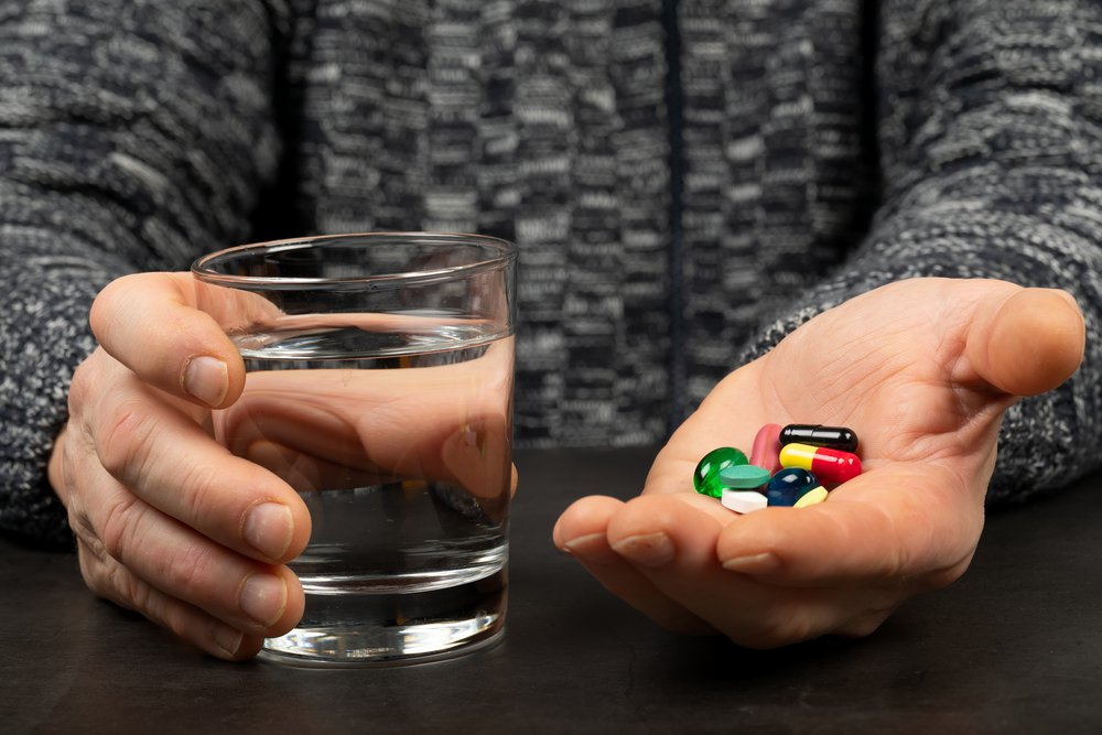 Photo of a senior patient hand holding colorful pills