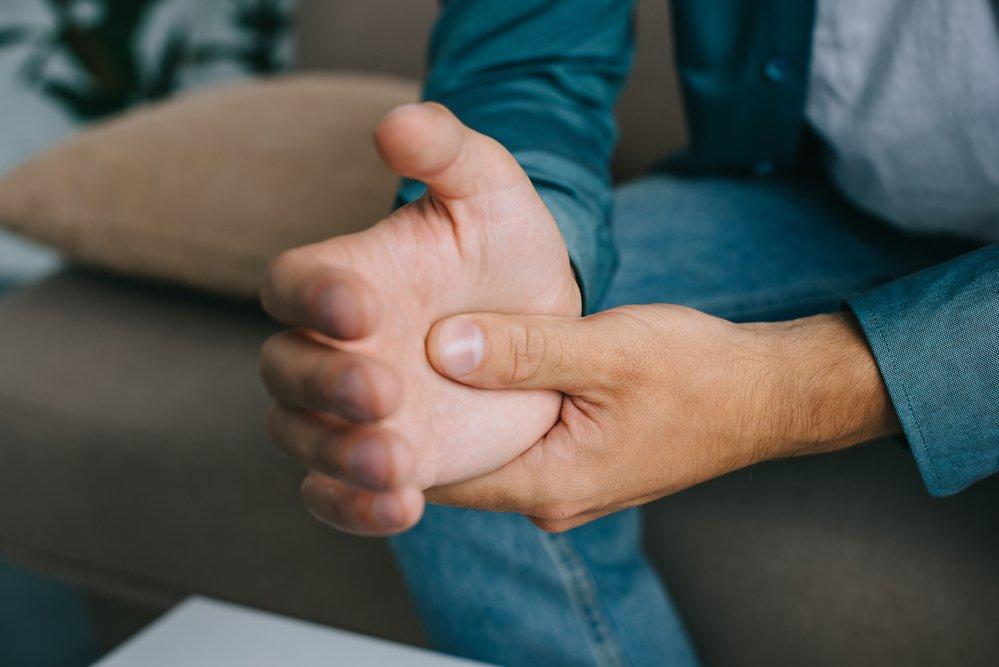 closeup partial view man having arthritis wrist pain using CBD