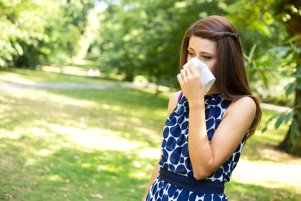 young woman with hay fever blowing her nose.