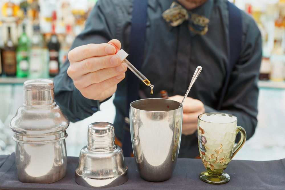 Bartender is making cocktail at bar counter, adding some CBD in the shaker