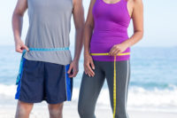 couple measuring weight loss on beach after using CBD