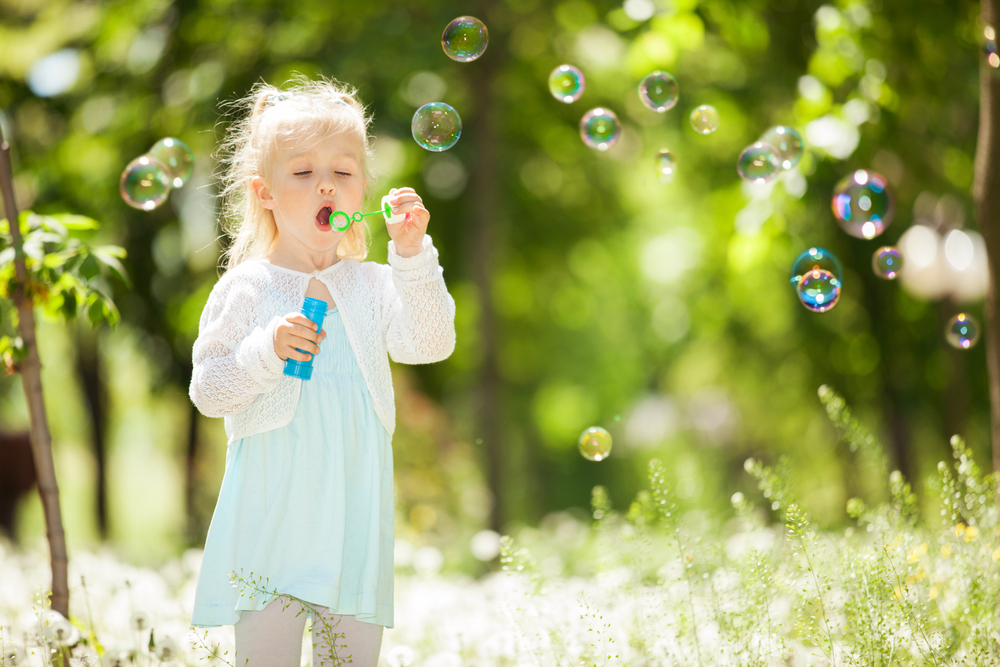Cute little girl blowing bubbles in the park