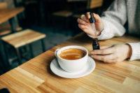 woman putting CBD drops into coffee